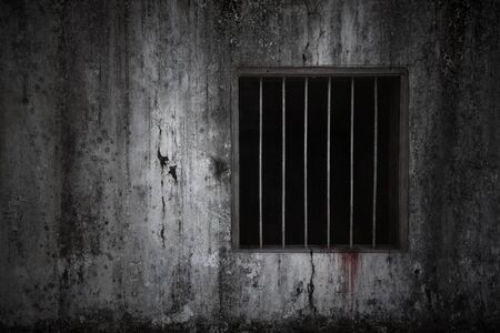 Bloody scary on the window with rusty bars on old grungy prison cell wall, concept of horror and Halloween Stock Photo
