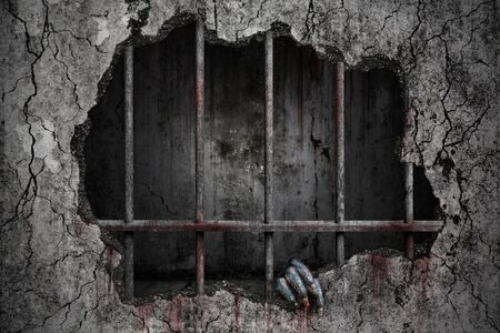Hand of devil has stains and drops of blood and holding the damaged grungy crack and broken concrete wall in old prison metal bars, Bloody background scary and horror