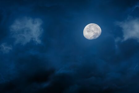 Moon at night with bright and dark clouds on blue background Stock Photo