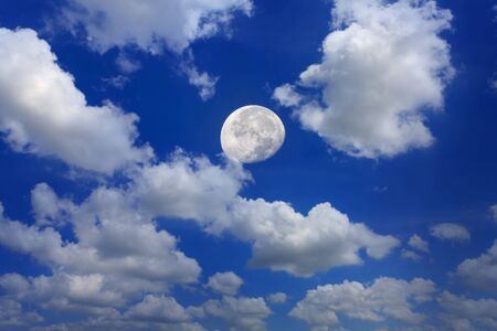 Moon in daytime in blue sky background with clouds