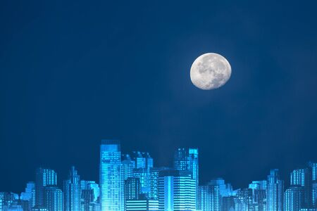 Moon with cityscape on clear blue background Stock Photo