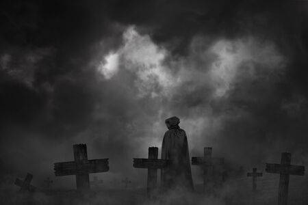 Scary background cemetery cross and the vampire in the hood stands back with dark silhouette, concept of horror and Halloween