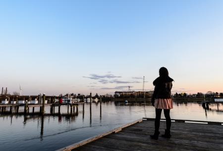 nastoletnie dziewczyny stojÄ…cej na starym molo morze o zmierzchu