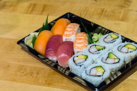 Delicious sushi rolls on black plate photo