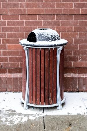 Nowoczesne bin drewniane pokryte śniegiem śmieci