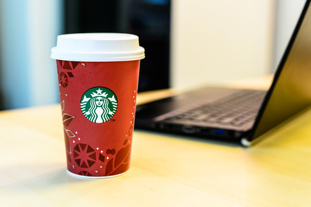 BOSTON, USA – DECEMBER 28, 2013: Photo of a Starbucks cup with a laptop. Starbucks is the largest coffee franchises in the world, currently. Editorial