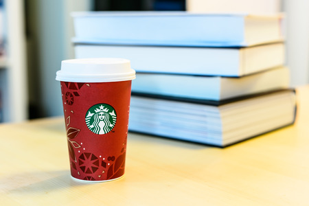 BOSTON, USA – DECEMBER 28, 2013: Photo of a Starbucks cup with a stack of textbooks. Starbucks is the largest coffee franchises in the world, currently.