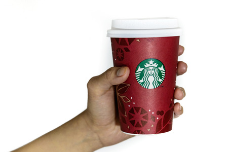 BOSTON, USA – DECEMBER 28, 2013: Photo of a Starbucks cup held with a hand. Starbucks is the largest coffee franchises in the world, currently.
