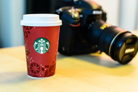 BOSTON, USA – DECEMBER 28, 2013: Photo of a Starbucks cup with a Nikon camera. Starbucks is the largest coffee franchises in the world, currently.