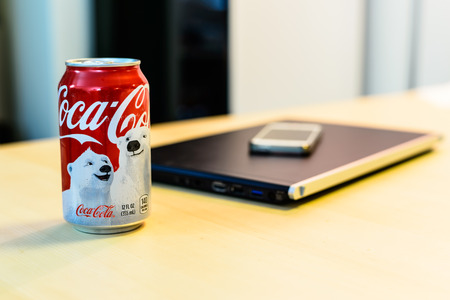 BOSTON, USA – DECEMBER 28, 2013: Photo of a Coca-Cola can with a laptop and smartphone. Coca-Cola was ranked on the 2011 Fortune Global 500, a list of the worlds largest companies. Editorial