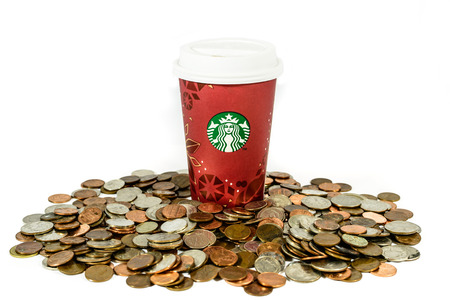 BOSTON, USA – DECEMBER 28, 2013: Photo of a Starbucks cup with coins. Starbucks is the largest coffee franchises in the world, currently.