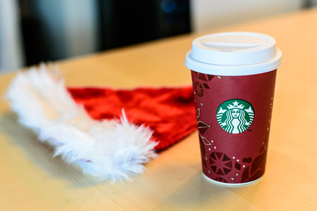 BOSTON, USA – DECEMBER 28, 2013: Photo of a Starbucks cup with a Santa Claus hat. Starbucks is the largest coffee franchises in the world, currently.