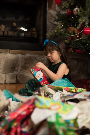 Child unwrapping gifts during Christmas 版權商用圖片