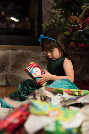 unwrapping: Child unwrapping gifts during Christmas Stock Photo
