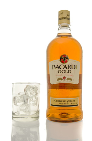 bacardi: Winneconne, WI - 10 March 2016: A bottle of Bacardi Gold rum with a empty glass of ice. Editorial