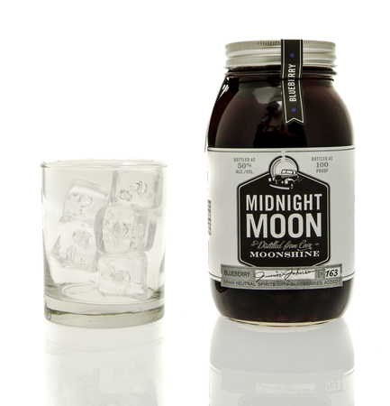 moonshine: Winneconne, WI - 15 March 2016:  A bottle of Midnight Moon moonshine with a glass of ice Editorial