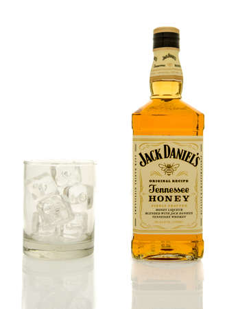 daniels: Winneconne, WI - 19 March 2016:  A bottle of Jack Daniels honey whisky with a glass of ice.
