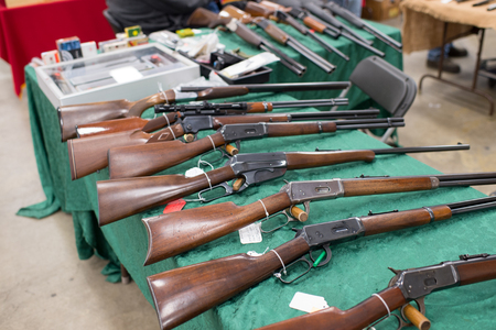 confiscated: Winneconne, WI - 17 April 2016:  Image of rifles on a table at a gun show.