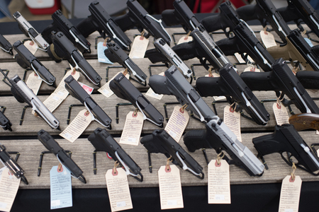 confiscated: Winneconne, WI - 17 April 2016:  Image of hand guns on a table at a gun show.