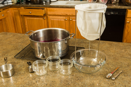 Items needed to make homemade jelly or jam at home.  Strainer, bowl, measuring cups, and kettle Stock Photo
