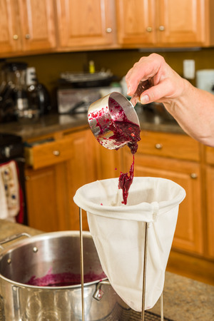 conserving: Pulp being poured into a strainer to separate the seeds and skin from the juice.