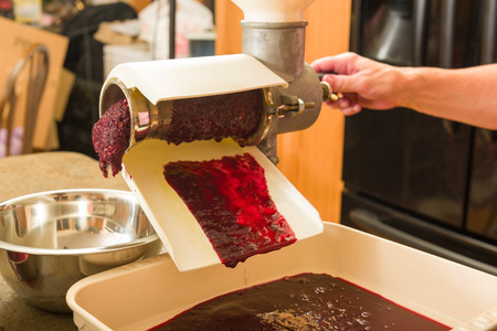 thru: Grape pulp going thru a food mill to get more juice from straining thru a bag alone can,