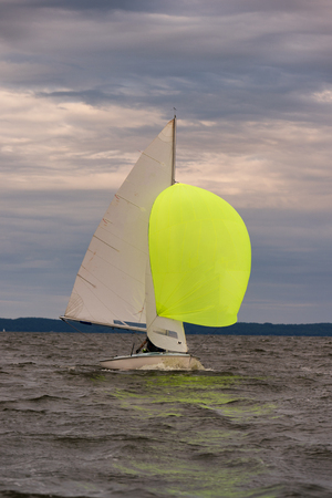 ship bow: Flying Scot sail boat on a body of water with its spinnaker up Stock Photo