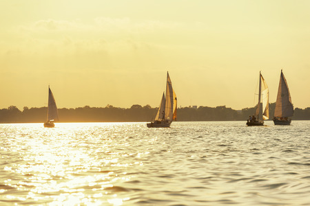 spinnaker: Sailboat on a lake as the sun sets