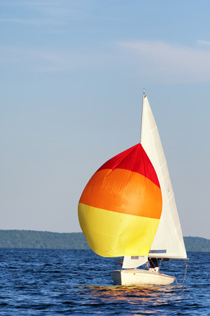spinnaker: A flying scot sail boat with its spinnaker up. Stock Photo