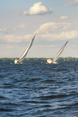 ship bow: Two sailboats lean heavy while racing towards the finish line.