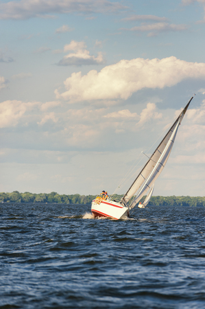 spinnaker: Sailboat is leaning while making a turn on a windy day.