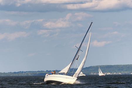 ヨットは、風の強い日にターンしながら傾いています。