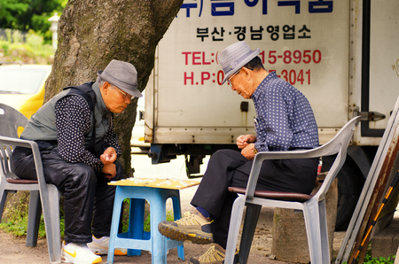 koreans: Busan, South Korea - 18 June 2011:  Two Korean men playing the popular game of Janggi.