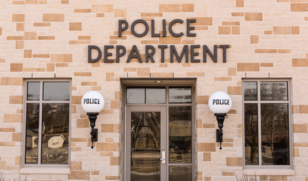 precinct station: Shot of a police station with lights on both sides of the door that say police on them.
