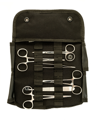 Surgical instrument kit on including hermostasts, scissors, holder, needle probe, and tweezers on an isolated background