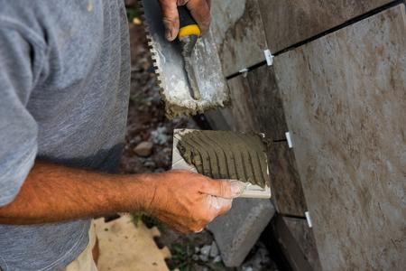 Mortel wordt aangebracht op een tegel met een gegroefde troffel zodat deze op het montageoppervlak blijft. Stockfoto