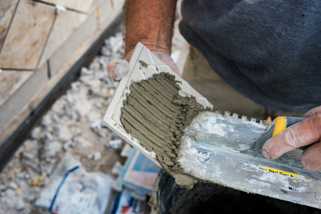 Mortar being applied to a tile with a grooved trowel for it to stick to the mounting surface.