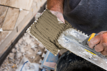 Mortel wordt aangebracht op een tegel met een gegroefde troffel zodat deze op het montageoppervlak blijft.