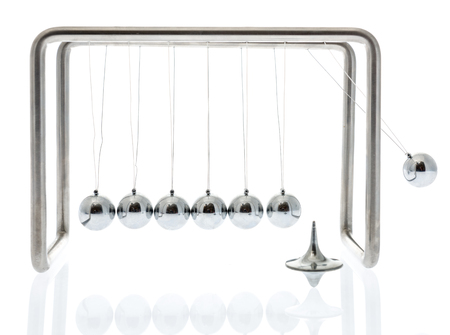 Physics at work with a Newton cradle swinging and a spinning top on an isolated background Stock Photo
