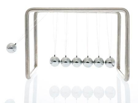 Newtons cradle swinging showing physics on an isolated background