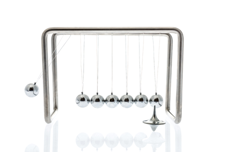 Physics at work with a Newton cradle swinging and a spinning top on an isolated background Standard-Bild