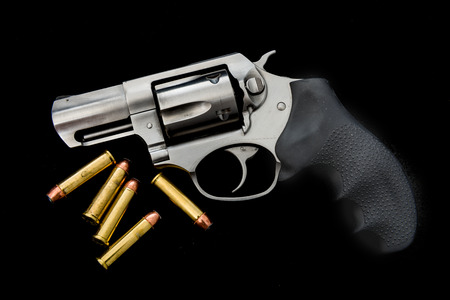 A 357 magnum revolver with ammunition on an isolated background