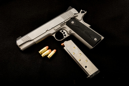 A 1911 with clip and ammunition on an isolated background