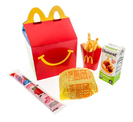 Winneconne, WI - 7 August 2018: A cheeseburger happy meal with honest kids apple juice and yogurt on an isolated background Redakční