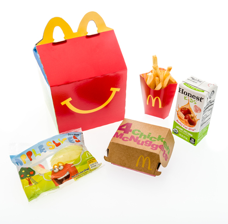 Winneconne, WI - 7 August 2018: A chicken McNugget happy meal with honest kids apple juice and apple slices on an isolated background Editorial