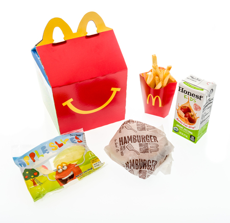 Winneconne, WI - 7 August 2018: A hamburger happy meal with honest kids apple juice and apple slices on an isolated background Redakční