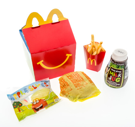 Winneconne, WI - 7 August 2018: A cheeseburger happy meal with chocolate milk  and apple slices on an isolated background Editorial