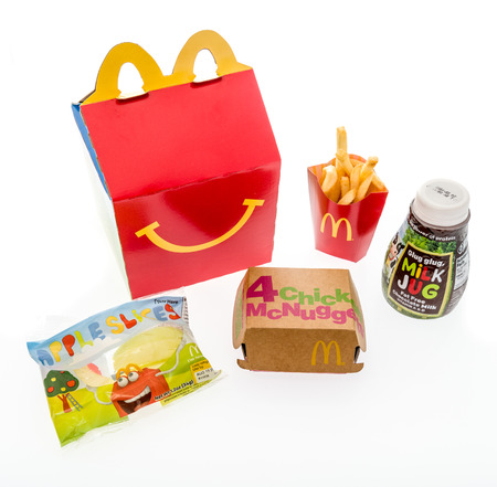 Winneconne, WI - 7 August 2018: A chicken McNugget happy meal with chocolate milk and apple slices on an isolated background