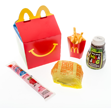 Winneconne, WI - 7 August 2018: A cheeseburger happy meal with chocolate milk and yogurt on an isolated background Editorial