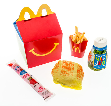 Winneconne, WI - 7 August 2018: A cheeseburger happy meal with white milk and yogurt on an isolated background
